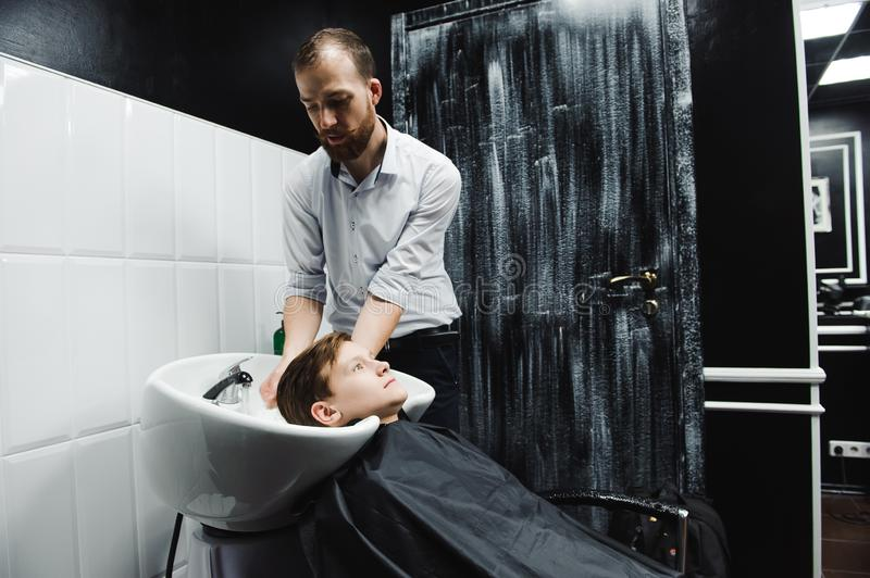 A boy is washed by the hairdresser in the barbershop. A boy is washed by the hairdresser in the barbershop royalty free stock photos