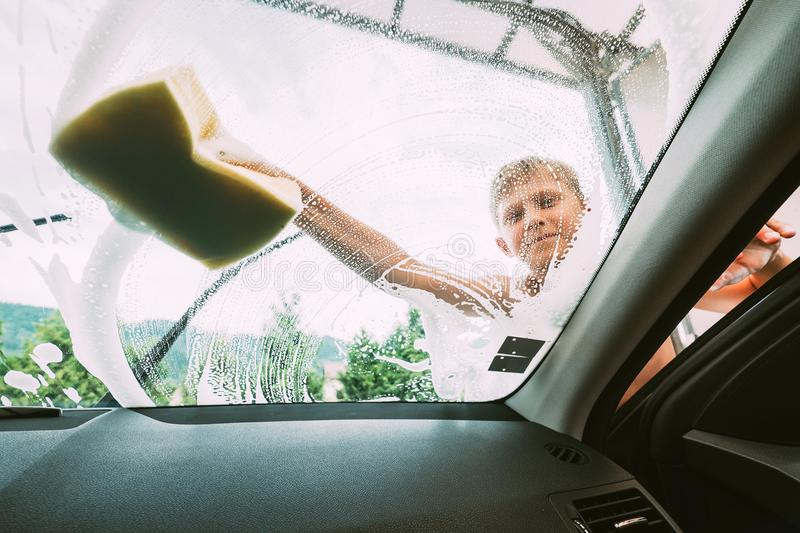 Boy washes front car window with sponge stock photography