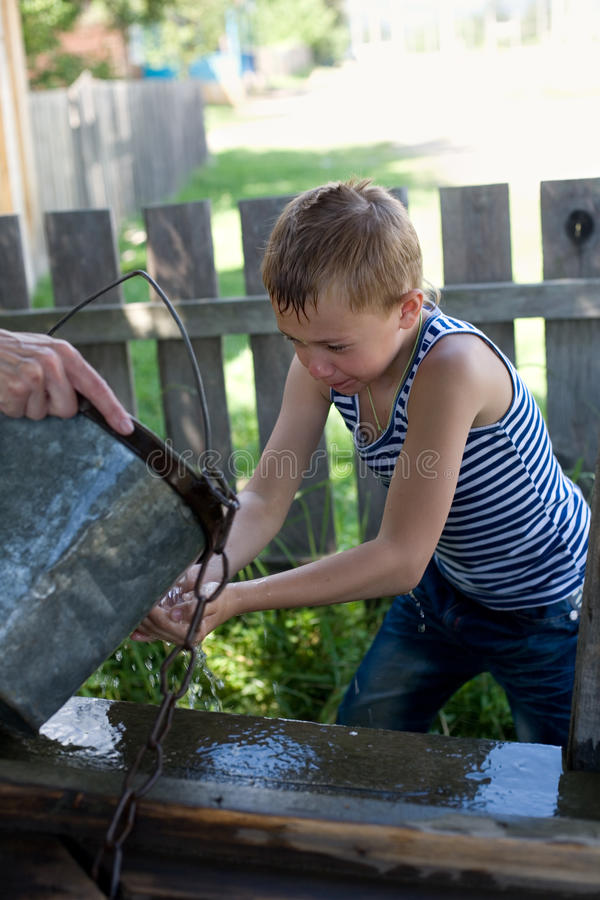 Boy washes well water. stock photos