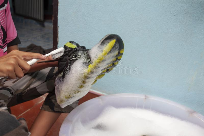 A boy washing the dirty shoes or sneakers in bubble filled basin. royalty free stock photography