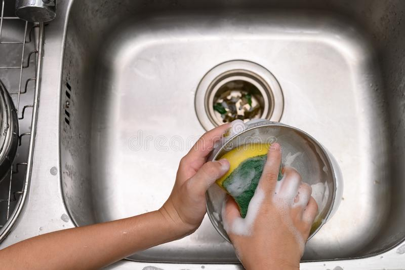 Boy washing dishware in the kitchen sink. With soapy sponge royalty free stock photography