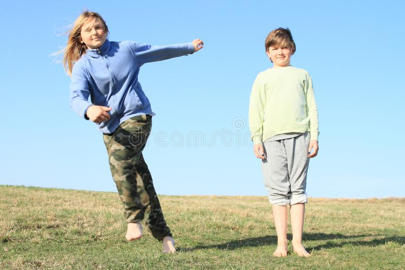 Boy watching dancing girl. Smiling kids - young barefoot girl with blond hair dressed in khaki pants and blue jacket dancing and jumping in front of barefoot royalty free stock photo