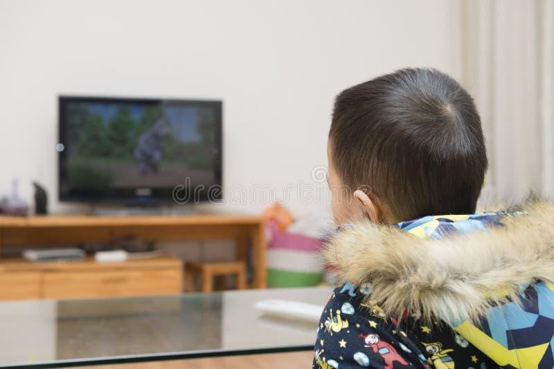 Boy watching cartoon TV stock photography