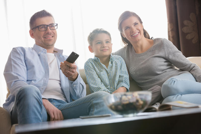 Boy watching TV with parents in living room stock photography