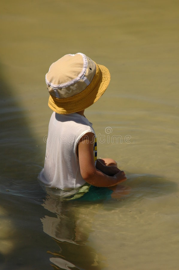 Boy in water stock photo