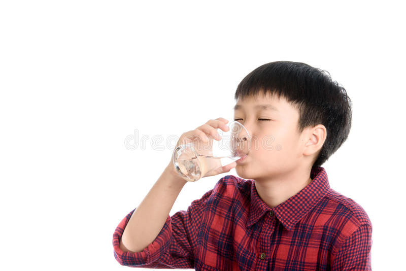 Boy and water. Young Thai boy drinking fresh water from glass on white background stock image