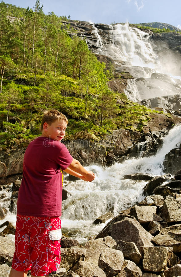 Boy at waterfall. stock images