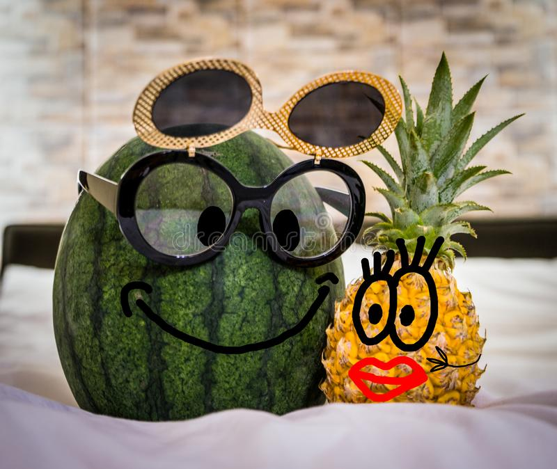 Boy Watermelon With Glasses And Girl Pineapple With Red Lips In Bed. Funny picture, couple having fun royalty free stock photos