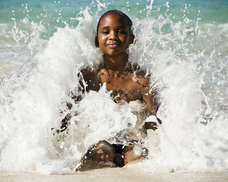 Boy in wave. Young bahamian boy sitting in crashing wave royalty free stock photos