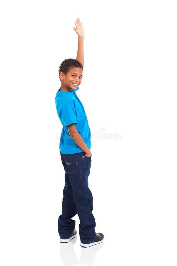 Boy waving goodbye. Happy little indian boy waving goodbye on white background royalty free stock image