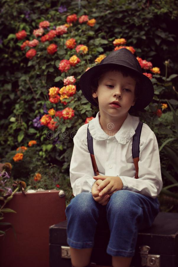 Boy Wearing Black Hat Sitting on Case Near Flowers stock images