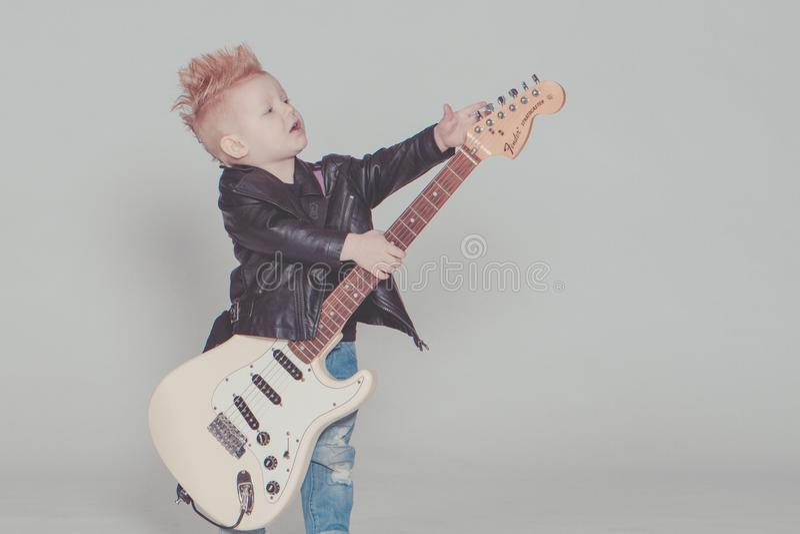 Boy Wearing Black Jacket Holding Electric Guitar royalty free stock photos