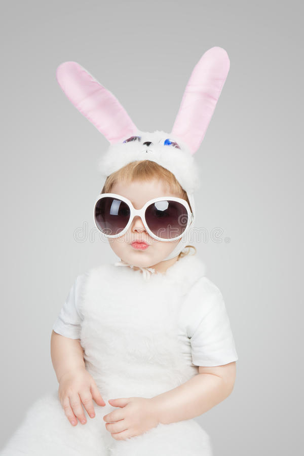 Boy wearing a bunny rabbit costume and sunglasses. Kiss lips. Studio shot gray background. 2 year white easter rabbit royalty free stock images