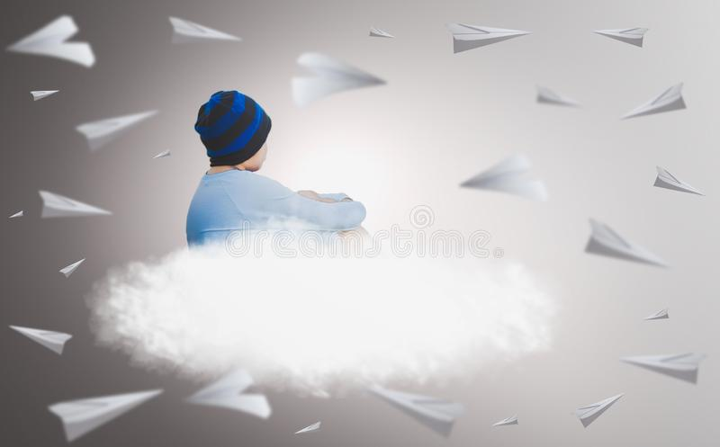 Boy wearing glasses wearing a blue hat, sitting on cloud that floating with paper plane of isolated gray background, imaginative stock photography