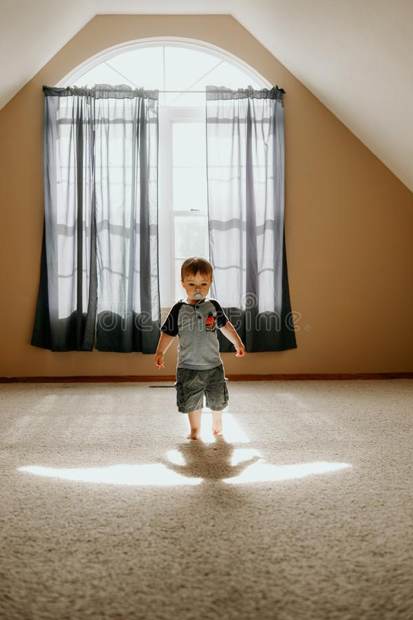 Boy Wearing Gray T-shirt and Gray Cargo Shorts Inside White Painted Wall Room stock images
