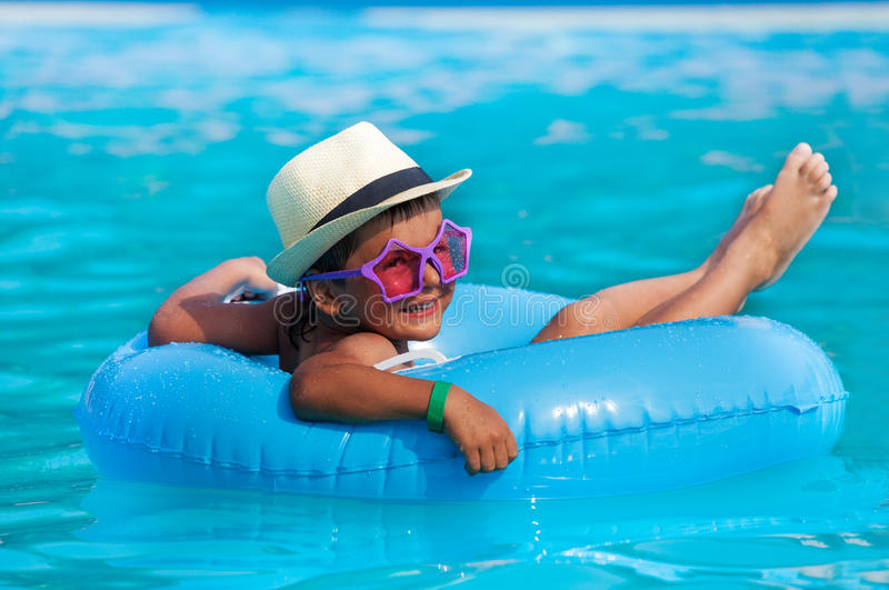 Boy wearing hat and glasses swimming in ring. Happy small boy wearing hat and glasses in inflatable ring swimming in pool outside during summer sunny day stock photos