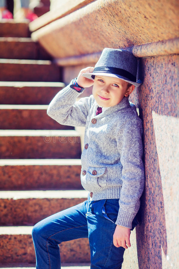 Boy wearing a hat. Happy stylish boy wearing a hat in the city stock images