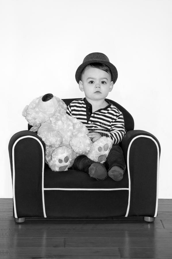 Boy wearing hat with teddy bear in black and white photography royalty free stock photos