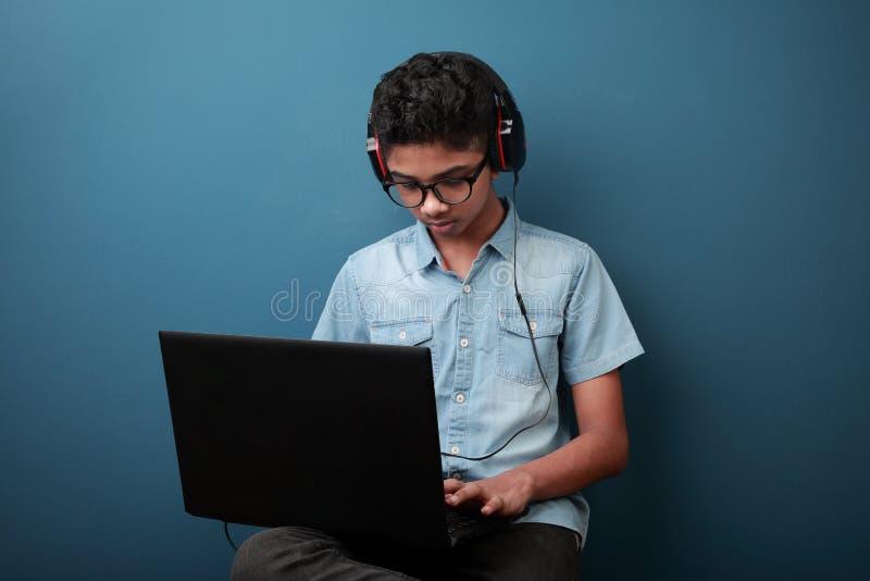 Boy wearing headset with laptop stock image
