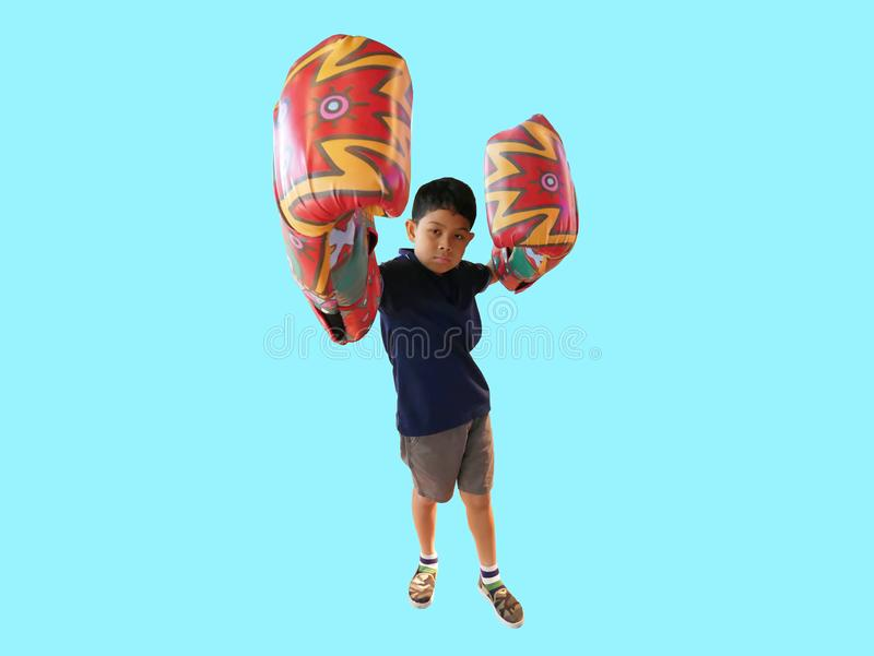 A Boy Wearing Huge Colorful Patterned Boxing Gloves Looking At Camera Isolated on Cyan royalty free stock photos