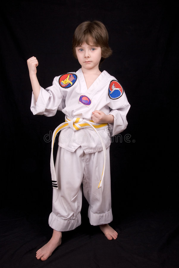 Boy Wearing martial arts Outfit. Attractive young boy Wearing Karate Outfit over a black background royalty free stock image