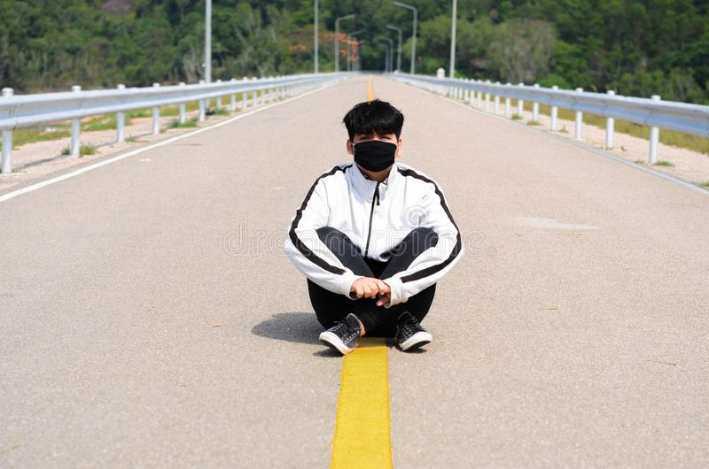 Boy wearing mask relax on the road after jogging. stock image