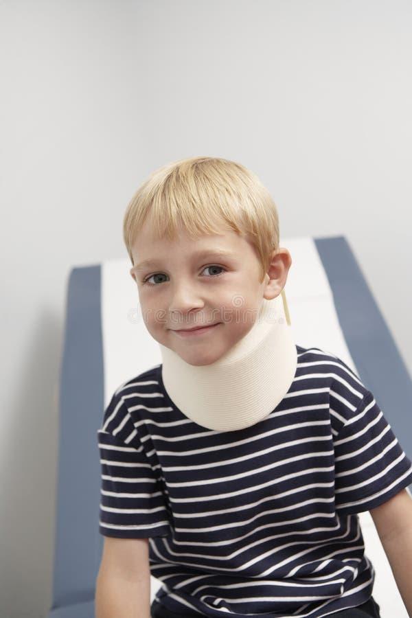 Boy Wearing Neck Brace. Portrait of a cute boy wearing neck brace in the clinic royalty free stock photos