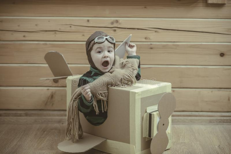 Boy wearing old-fashioned aviator hat. Scarf and goggles flying a cardboard airplane in his imagination stock photos