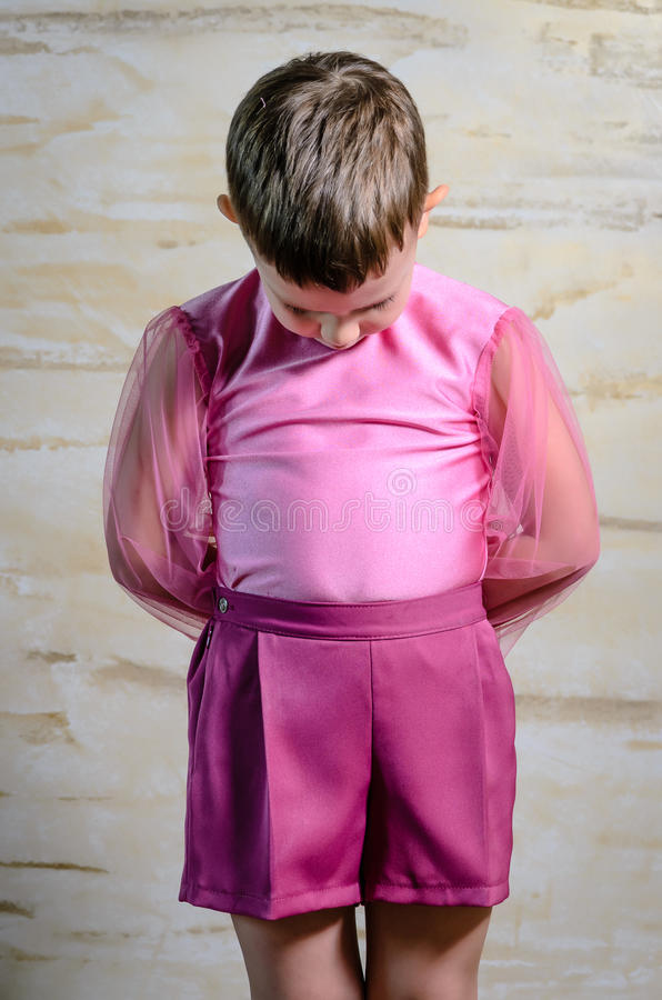 Boy Wearing Pink Dance Outfit with Head Bowed. Young Boy Wearing Pink Dance Costume Standing with Head Bowed and Hands Behind Back, Portrait of Traditional stock image