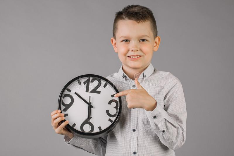 Boy wearing a plaid shirt and holding a watch, on a gray wall background, children portrait Studio. People sincere emotions, the royalty free stock photos