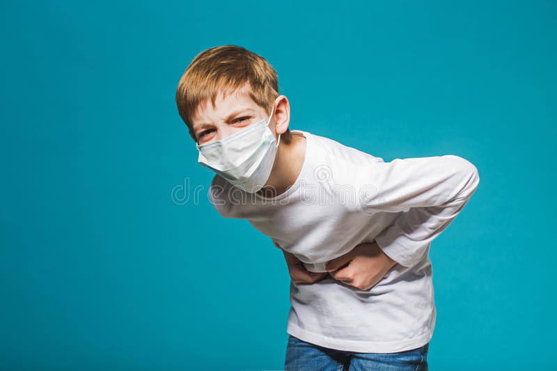 Boy wearing protection mask having stomach ache. Boy in white wearing protection mask having stomach ache stock images