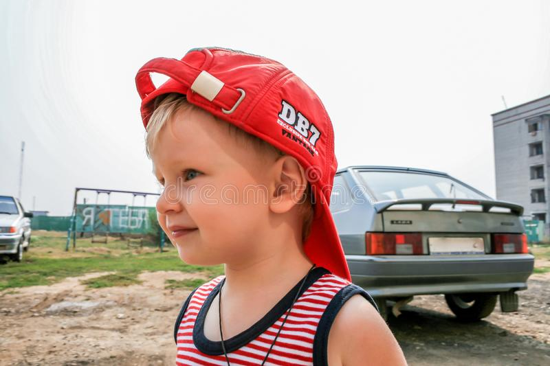 A boy wearing red baseball cap by the car, side view. royalty free stock photo