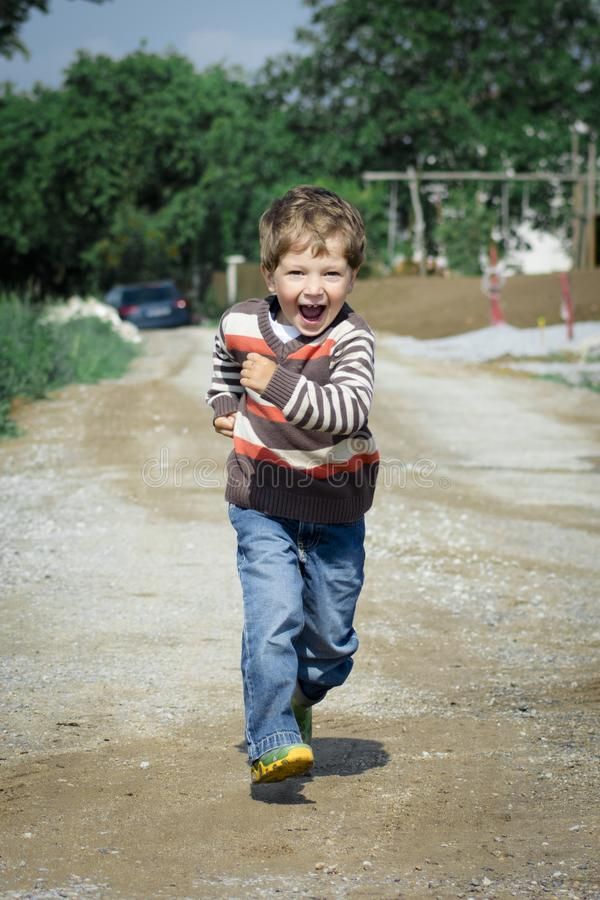 Boy Wearing Red, Brown, and White Stripe Sweater Running Photo royalty free stock photo