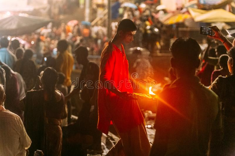 Boy wearing red cloth walking with lighted candle for blessing people in Varanasi Ganga Aarti at Holy Dasaswamedh Ghat. Boy wearing red cloth walking with stock photos