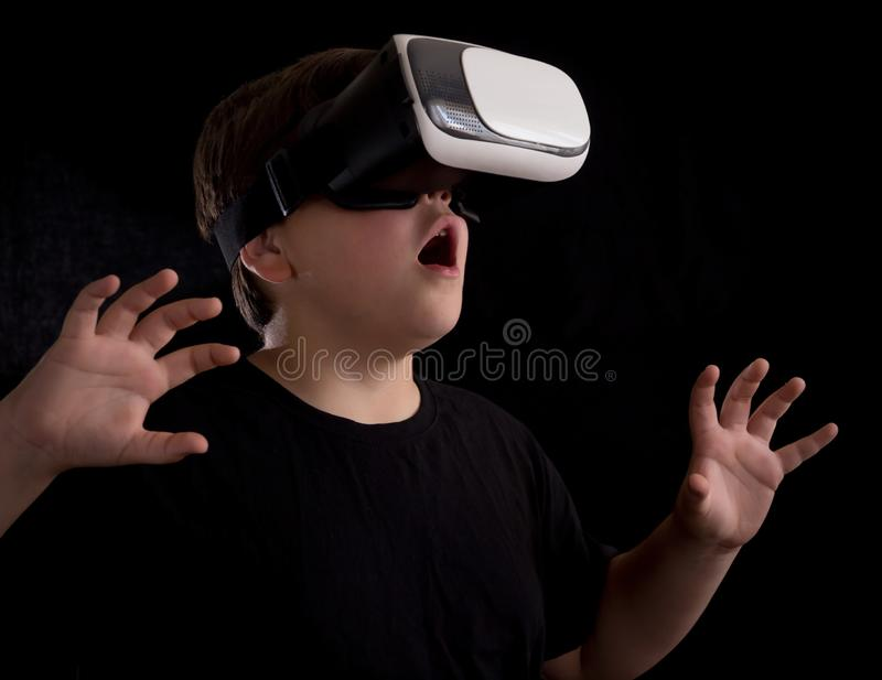 Boy wearing a virtual reality glasses surprised by what he is seeing in the simulation or game, isolated on black background stock photos