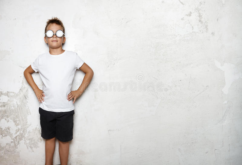 Boy wearing white tshirt, shorts stands on a wall stock images