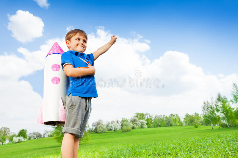 Boy wears paper rocket toy and holds arm up royalty free stock images