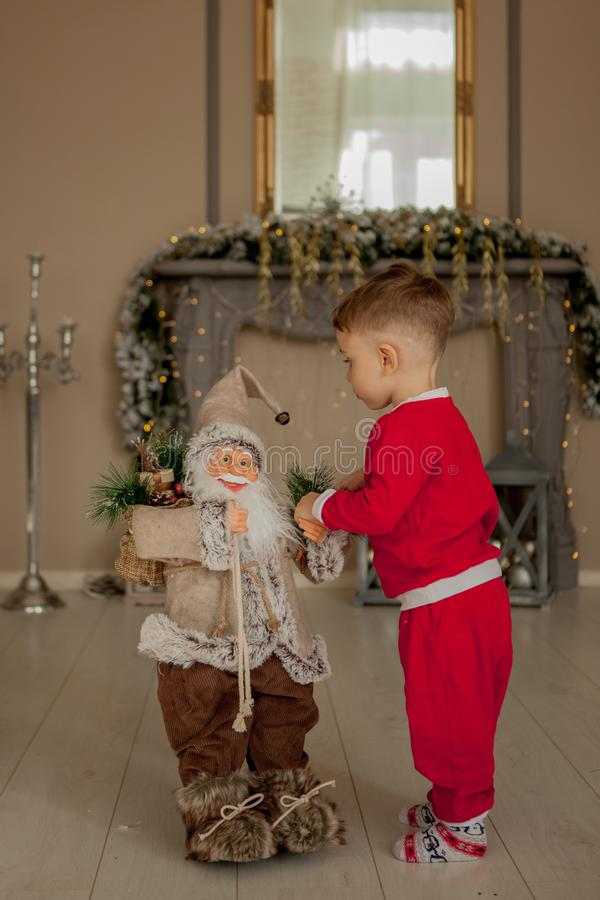 Boy is welcome with santa. Holidays, present, childhood, happiness concept stock photo