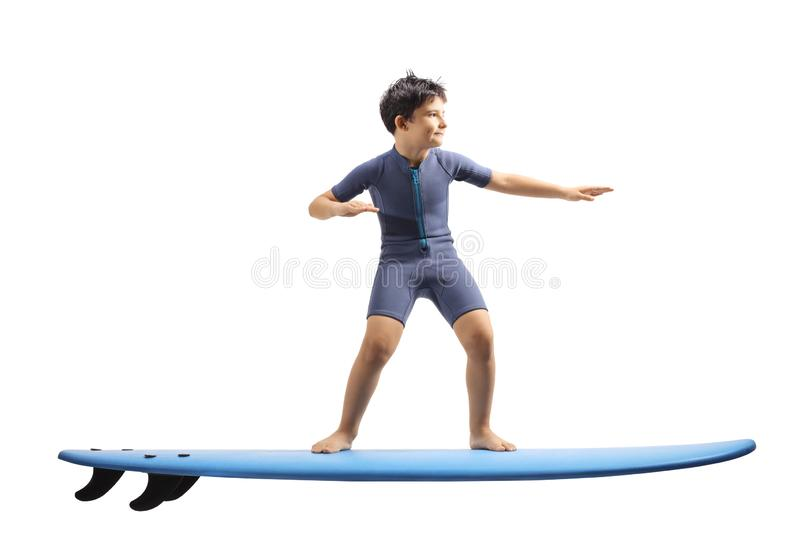 Boy in a wetsuit standing on a surfing board. Full length shot of a boy in a wetsuit standing on a surfing board isolated on white background stock photos