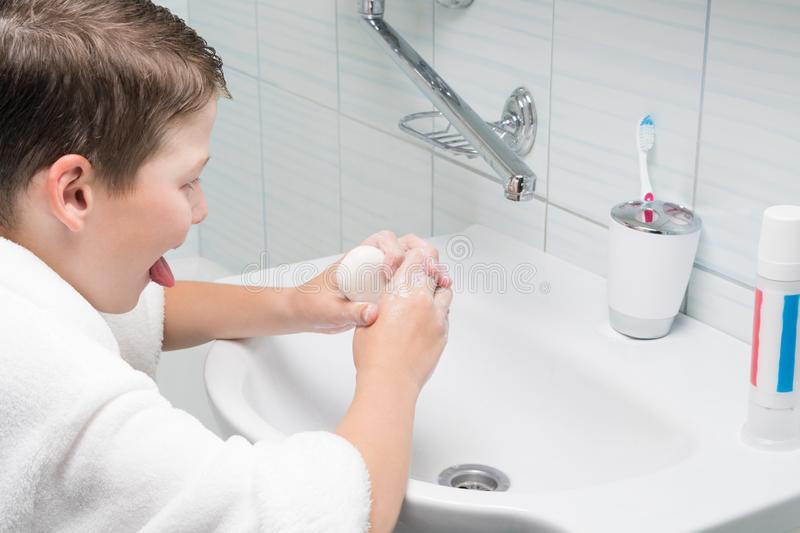 A boy in a white bathrobe in the bathroom washes his hands with a bar of soap in the sink royalty free stock image