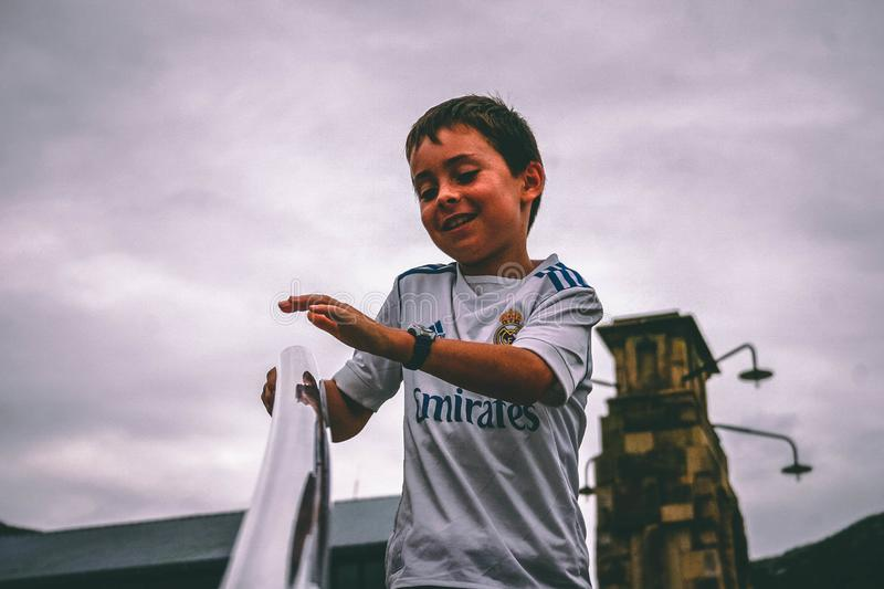 Boy in White and Blue Fly Emirates Jersey Shirt Holding on Stairs Grab Bar Under Gray Skies stock photos