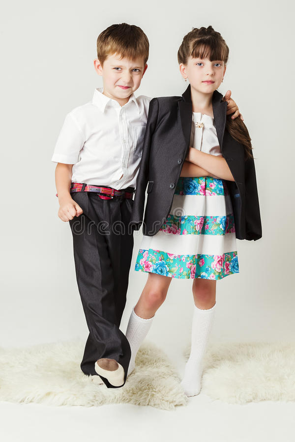 Boy in white shirt hugs a girl by the shoulder stock photos