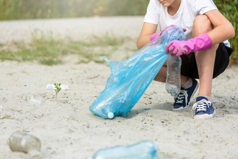 Boy in white t shirt in gloves collects garbage and plastic bottles into blue package on the beach. Young volunteer royalty free stock images