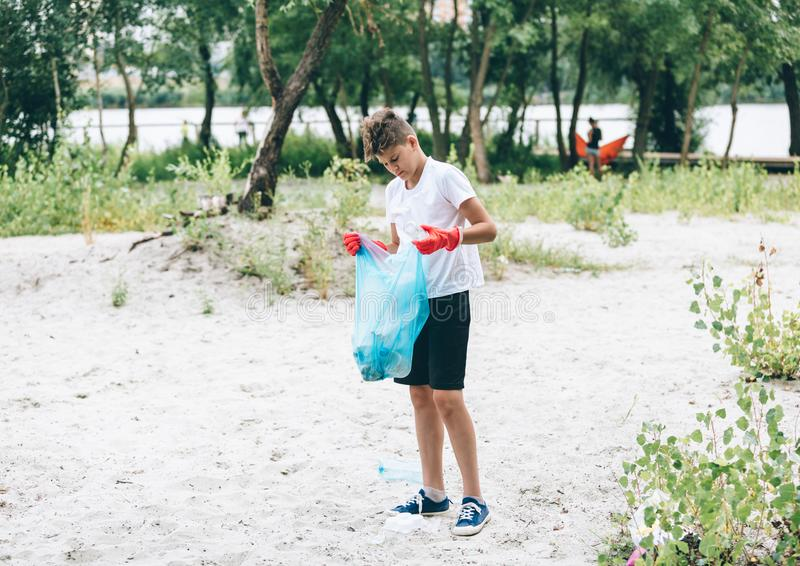 Boy in white t shirt in gloves collects garbage and plastic bottles into blue package on the beach. Young volunteer royalty free stock image