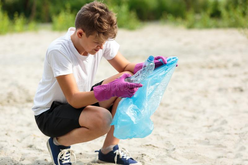 Boy in white t shirt in gloves collects garbage and plastic bottles into blue package on the beach. Young volunteer. Environment. Al protection, save environment royalty free stock photography