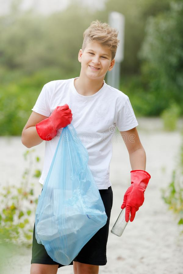 Boy in white t shirt in gloves collects garbage and plastic bottles into blue package on the beach. Young volunteer. royalty free stock image