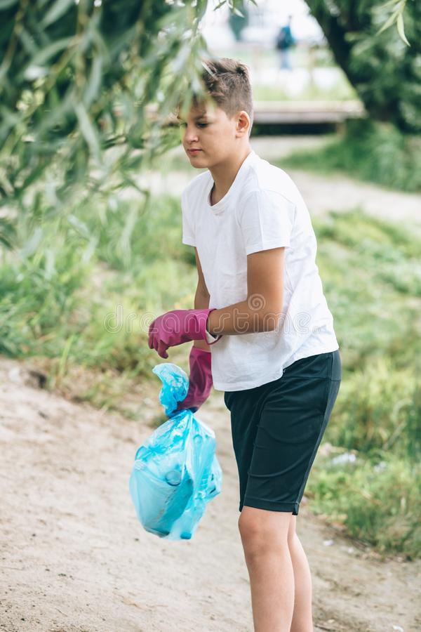 Boy in white t shirt in gloves collects garbage and plastic bottles into blue package on the beach. Young volunteer stock images