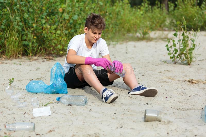 Boy in white t shirt in gloves collects garbage and plastic bottles into blue package on the beach. Young volunteer. royalty free stock photography