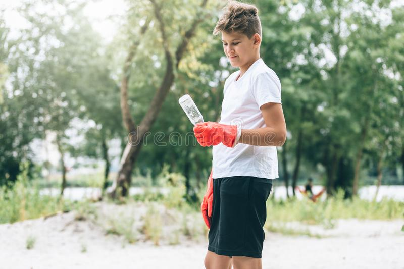 Boy in white t shirt in gloves collects garbage and plastic bottles into blue package on the beach. Young volunteer royalty free stock photo