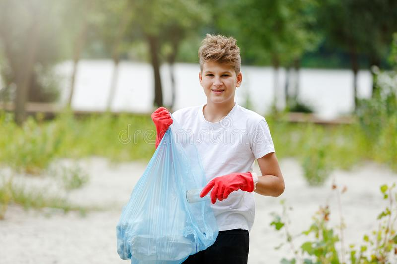 Boy in white t shirt in gloves collects garbage and plastic bottles into blue package on the beach. Young volunteer royalty free stock photos